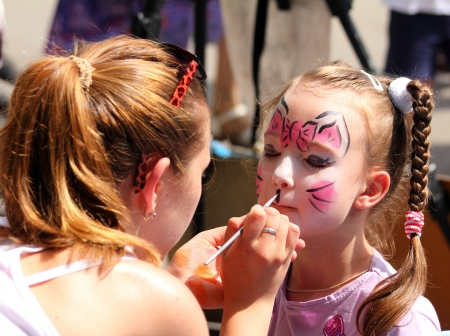 kids painting: artist paints butterfly on face of cute little girl Stock Photo
