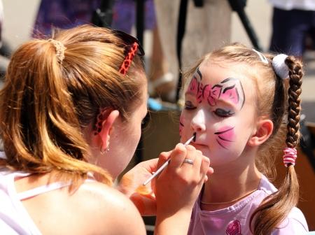 Künstler malt Schmetterling auf dem Gesicht des netten kleinen Mädchens