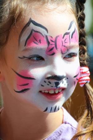 peinture visage: mignonne petite fille avec le maquillage de chat visage peint