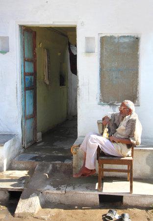 UDAIPUR, INDIA - NOVEMBER 24: Elderly Indian man sits outside his home. November 24, 2012 in Udaipur, Rajasthan, India