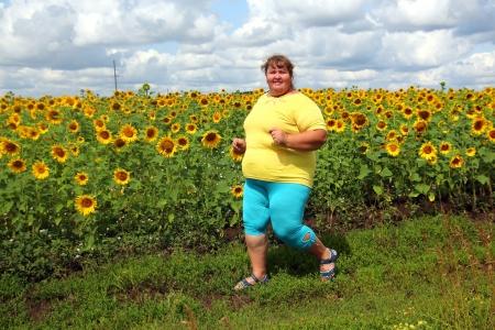 fitness - overweight woman running along field of sunflowers Stockfoto