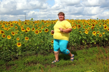 fitness - overweight woman running along field of sunflowers Standard-Bild