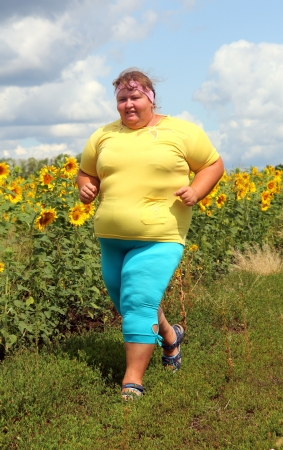 fitness - overweight woman running along field of sunflowers 스톡 콘텐츠