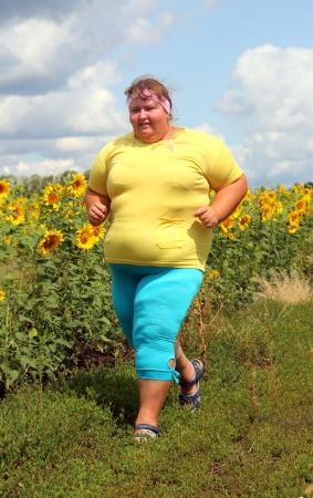 fitness - overweight woman running along field of sunflowers Foto de archivo