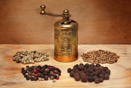 grinder and various spices on a wooden board photo
