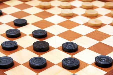 boardgames: checkerboard with checkers spaced close-up
