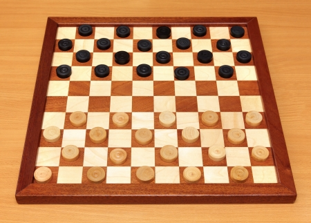 draught: wooden checkerboard with checkers spaced on table Stock Photo