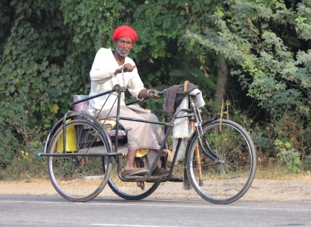 AGRA, INDIA - NOVEMBER 16, 2012: Old indian man on bike with manual drive in Agra, India, 16 nov 2012