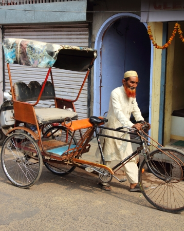 AGRA, INDIA - NOVEMBER 16, 2012: Old indian man rickshaw rolls his bike on street in Agra, India, 16 nov 2012