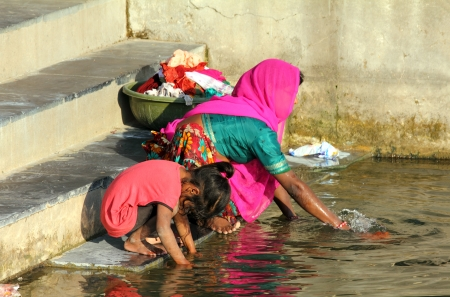 Indian woman with her daughter washing clothes in lake photo