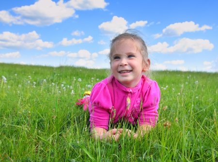 happy smiling little girl lying on green grass photo