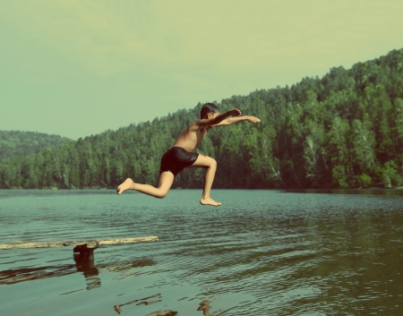 boy jumping in lake at summer vacations - vintage retro style Stock Photo
