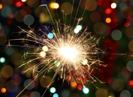 night stick: sparkler burning on background decorated Christmas tree