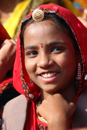 PUSHKAR, INDIA - NOVEMBER 21 2012: Portrait of smiling Indian girl in colorful ethnic attire at Pushkar camel fair