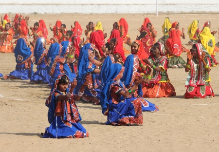 PUSHKAR, INDIA - NOVEMBER 21 2012: Indian girls in colorful ethnic attire dancing at Pushkar camel fair