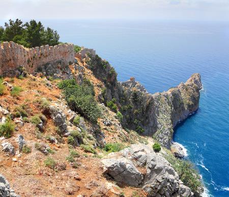headland: rocky headland in the sea and fortress wall in Alanya Turkey
