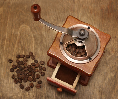 vintage coffee grinder and beans on old wooden background photo
