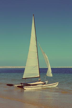 sailing catamaran on sea beach - vintage retro style photo