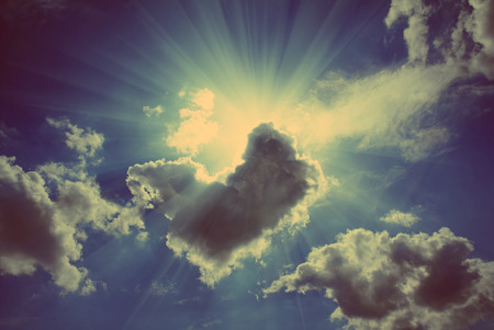 sun rays on dramatic sky wth clouds - vintage retro style photo