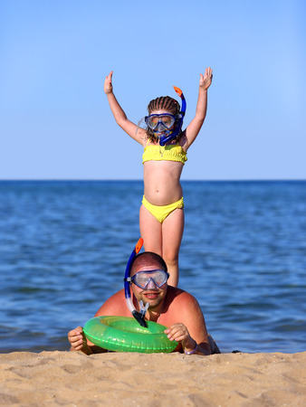 vacations - father and daughter on beach in scuba mask photo