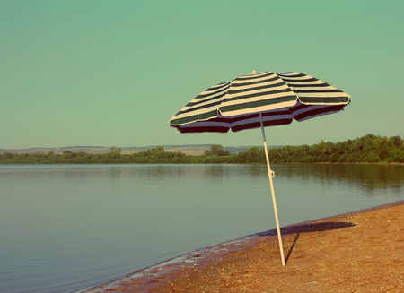 sun umbrella on empty sandy river beach - vintage retro style
