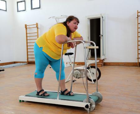 vermoeide dikke vrouw op trainer loopband - fitness