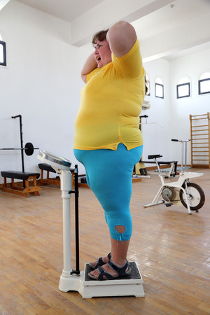 abstinence: impressed overweight woman standing on scales in the gym