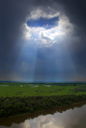 landscape with river and hole in dark clouds - view from height  photo