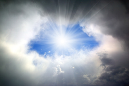 the through: sun shining through hole in the dark clouds  Stock Photo