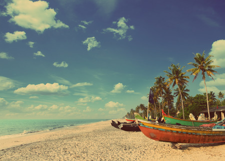 old fishing boats on beach in kerala india - vintage retro style photo