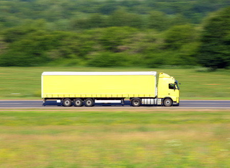 yellow truck driving on a road - slow shutter  photo