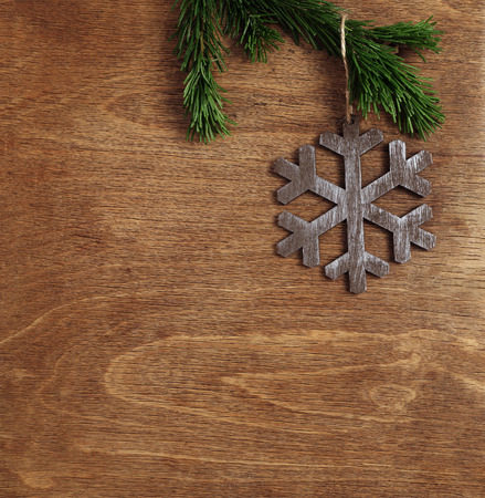 christmas wooden background with snowflake hanging on fir branch photo