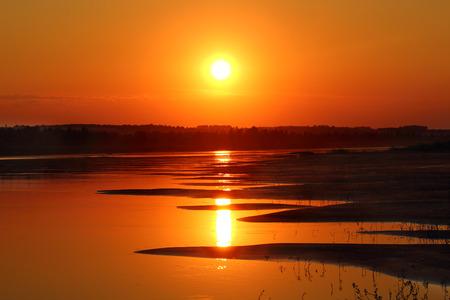beautiful orange sunset with waved river sand beach photo