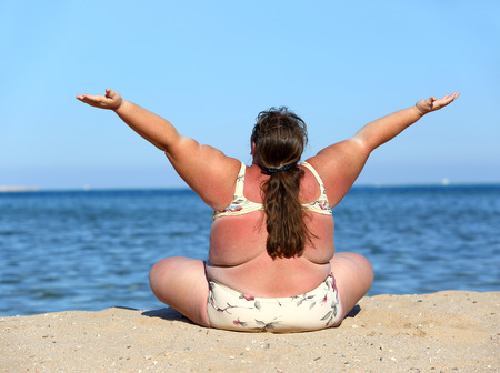 overweight woman sitting on beach with hands up