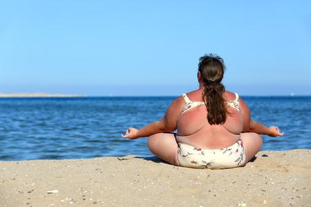 overweightl woman meditation on beach near sea Stock Photo