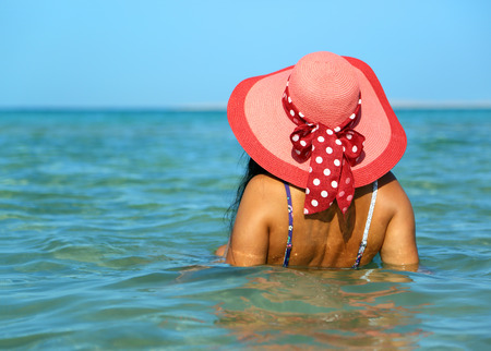 Young woman in red hat on the beach photo