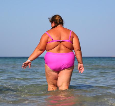 gordo: ba�o de mujer con sobrepeso en el mar - vista desde atr�s