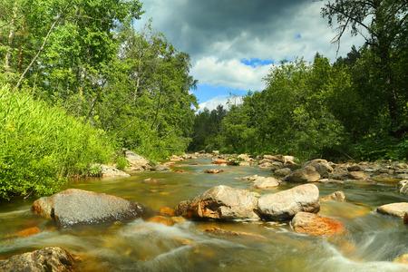 the clear sky: paisaje con río de montaña que fluye sobre rocas en verano