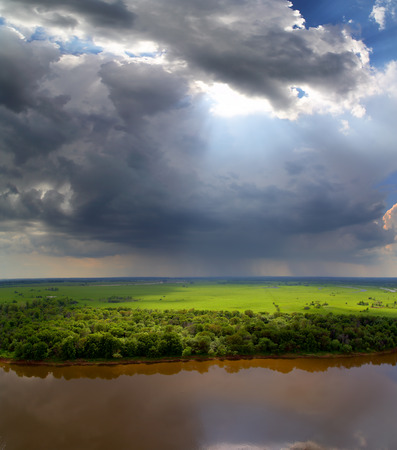 landscape with storm clouds, river and rain on horizon photo