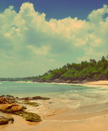 beautiful landscape with sea waves on tropical beach with stones and rocks - vintage retro style photo