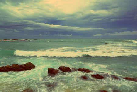 Beautiful sea stormy landscape over rocky coastline in Indian ocean - vintage retro style photo