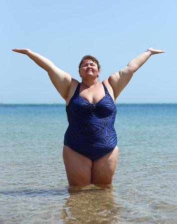 mujeres gordas: mujer con sobrepeso de pie en el mar en la playa con las manos en alto