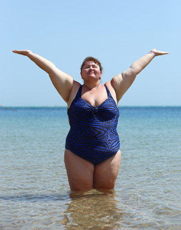 only 1 woman: overweight woman standing in sea on beach with hands up