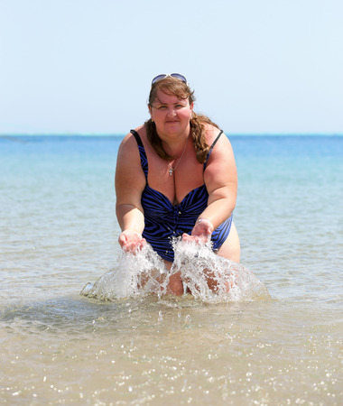 woman in bath: overweight woman bath in sea and splash Stock Photo