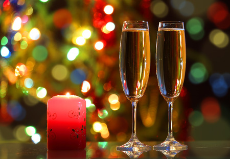 christmas candles: glasses with champagne and candle - romantic evening