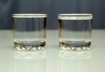 bebidas alcohÓlicas: dos vasos llenos de vodka de pie sobre una mesa de cristal