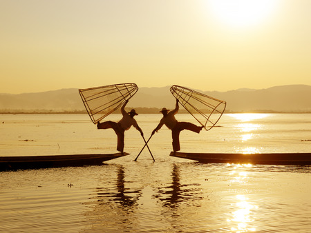 distinctive: Myanmar travel attraction landmark - Traditional Burmese fishermen with fishing net at Inle lake in Myanmar famous for their distinctive one legged rowing style
