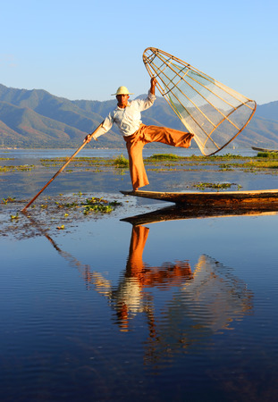 and distinctive: Myanmar travel attraction landmark - Traditional Burmese fisherman with fishing net at Inle lake in Myanmar famous for their distinctive one legged rowing style