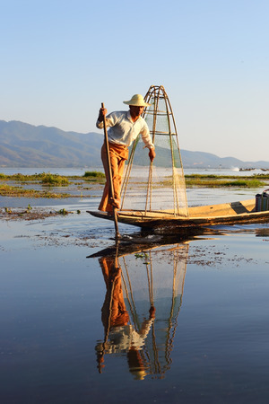 legged: Myanmar travel attraction landmark - Traditional Burmese fisherman with fishing net at Inle lake in Myanmar famous for their distinctive one legged rowing style