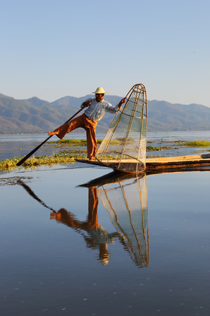 distinctive: Myanmar travel attraction landmark - Traditional Burmese fisherman with fishing net at Inle lake in Myanmar famous for their distinctive one legged rowing style